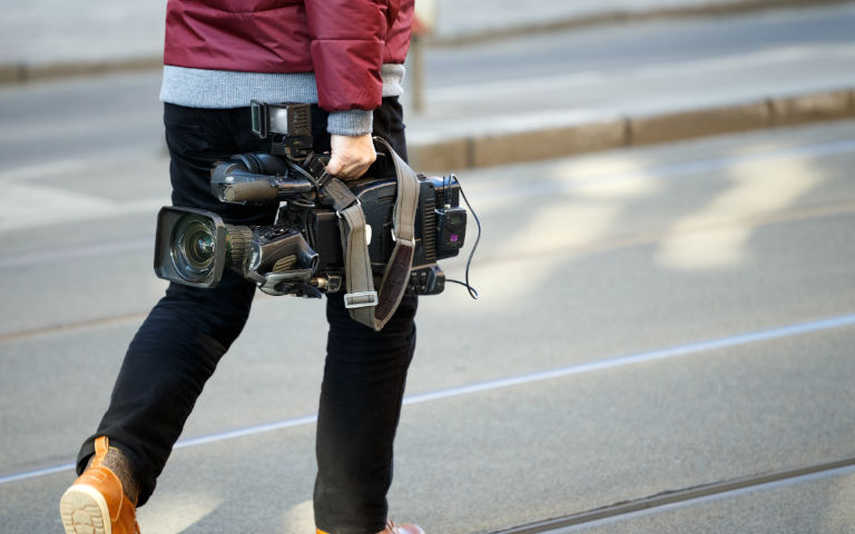 Person walking on street holding professional video camera