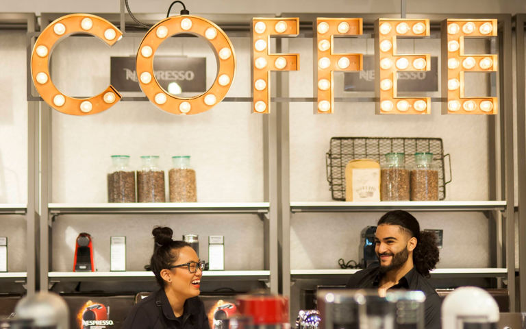 Two baristas laughing together
