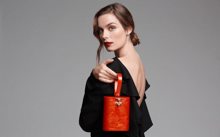 Une femme tenant un sac à main rouge
