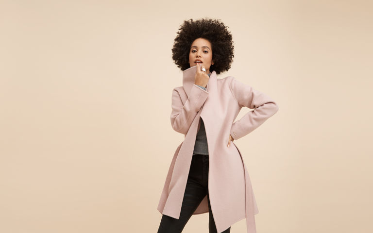 Woman model posing with pink coat for fashion shoot